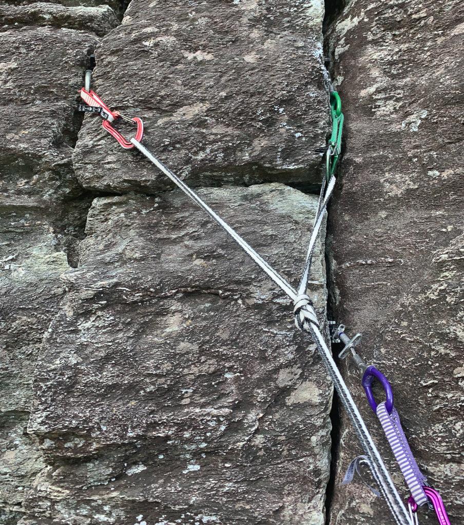 A three-piece climbing anchor in a block of rock.
