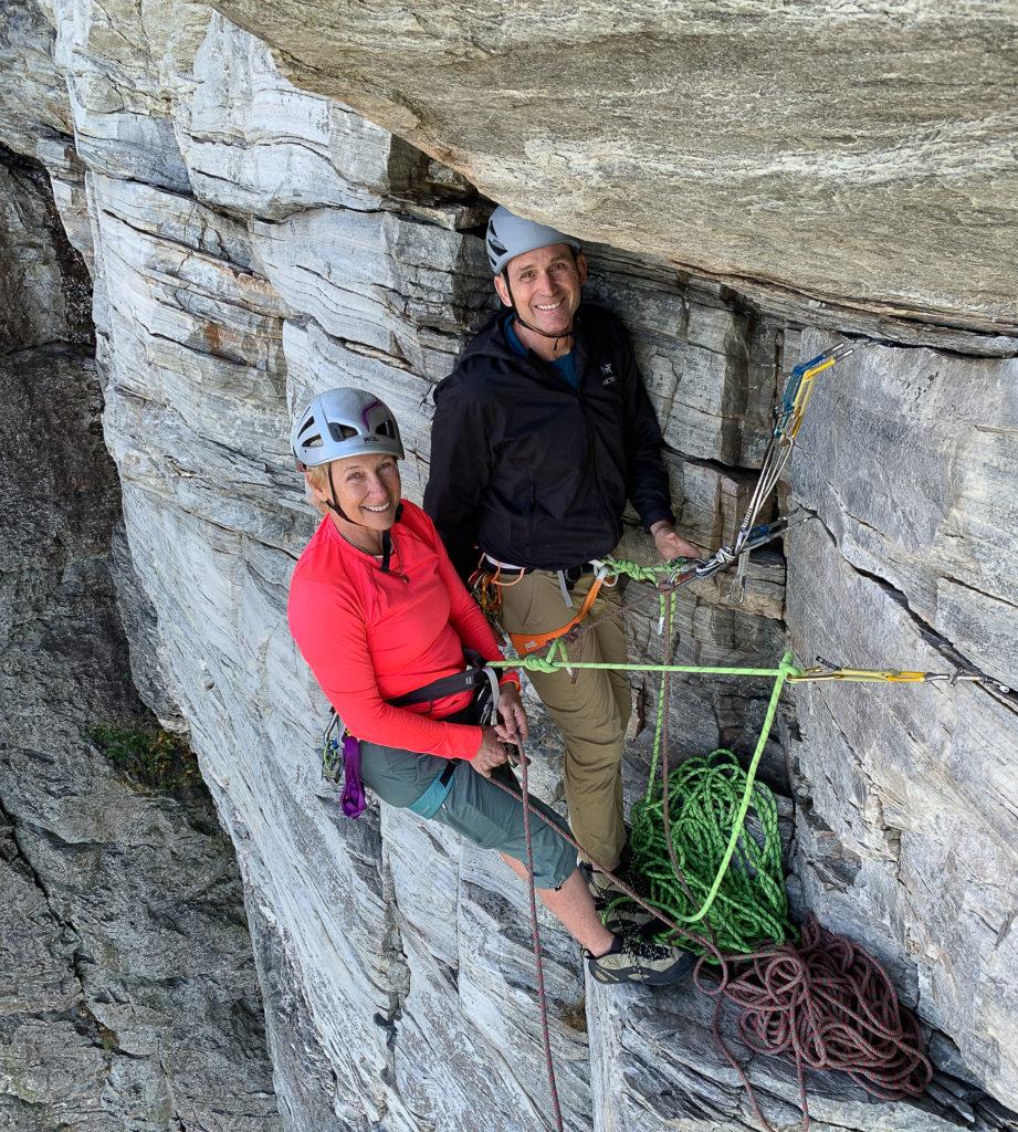 Three people using a climbing anchor in steep terrain.